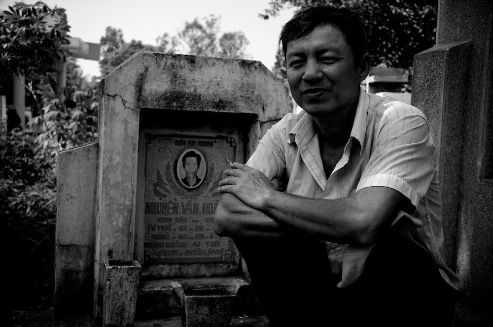 Ho Chi Minh City, Vietnam 2009. The grounds of Binh Hung Hoa Cemetery. He visits his brother's grave, and requests a portrait. Portraits and people of Vietnam.