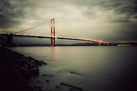 The  Golden Gate Bridge early in a misty evening, as seen from Crissy Field, San Francisco, California, USA...