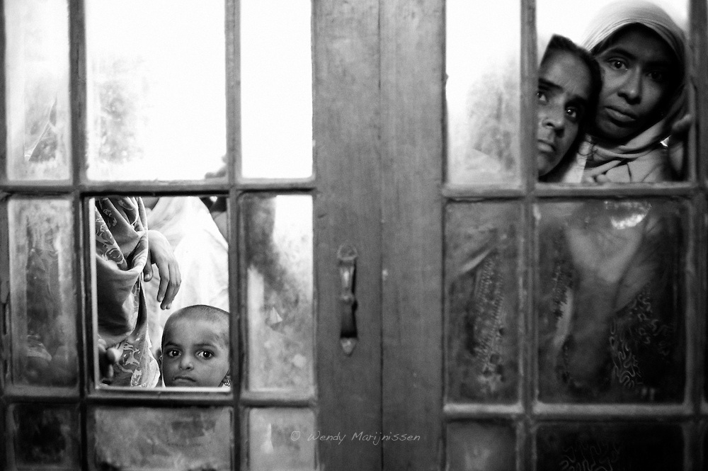 Women and children wait outside the doctors office inside the Shikarpur high school now housing families affected by the recent floods. Shikarpur, Pakistan, 2010.