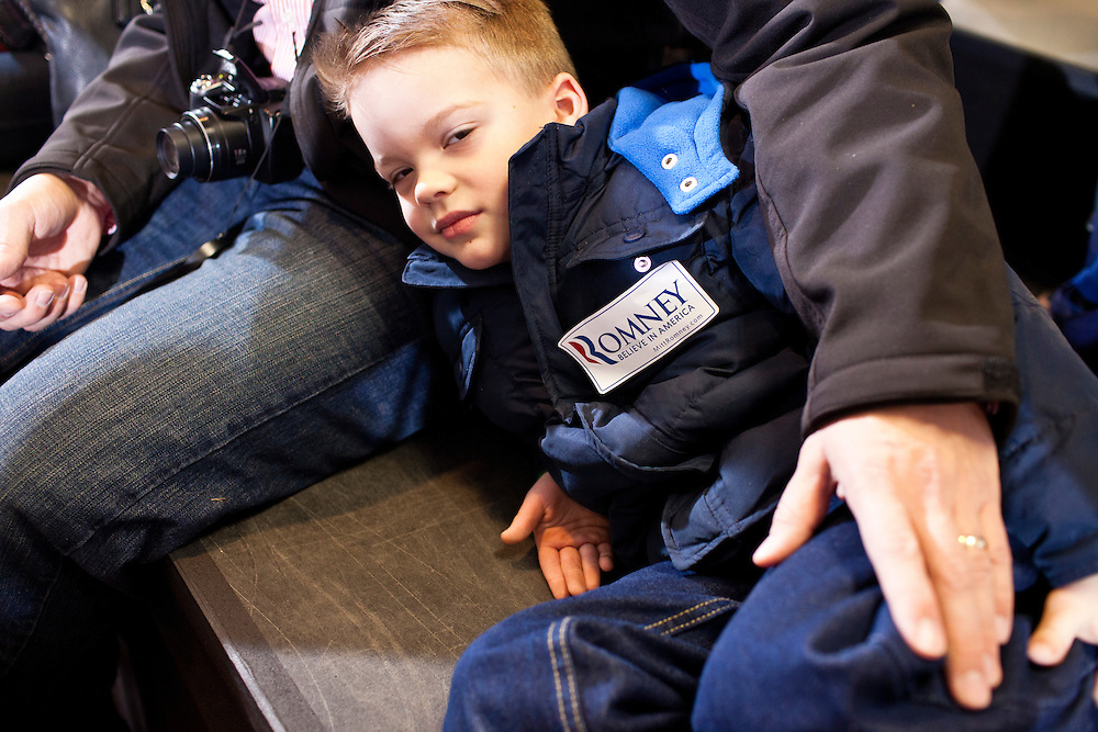 A young boy sits with his father as they wait for Republican presidential candidate Mitt Romney to arrive for a campaign rally at the Mississippi Valley Fairgrounds on Monday, January 2, 2012 in Davenport, IA.