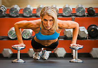 Physically fit woman doing pushups on dumbells in a healthclub.
