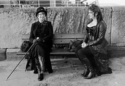 © Licensed to London News Pictures.01/11/15<br /> Whitby, UK. <br /> <br /> Two women wearing goth clothing sit on a bench as hundreds of visitors attend the Whitby Goth weekend in Whitby, North Yorkshire. The event began in 1994 to celebrate goth culture and music and takes place twice each year. <br /> Thousands of extravagantly dressed people attend the popular event wearing Steampunk, Cybergoth, Romanticism, Victoriana and other clothing as they take part in the celebration of Goth culture. <br /> <br /> Note to Editors - Picture shot on Kodak Tri X 400ISO film.<br /> Photo credit : Ian Forsyth/LNP