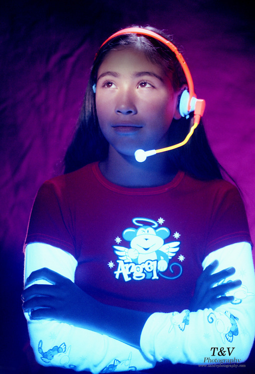 Young girl with glowing phone head gear.Black light