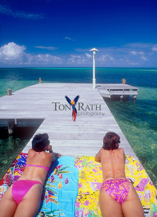Two young woman sunbathing on dock at Lighthouse Reef Resort, Belize