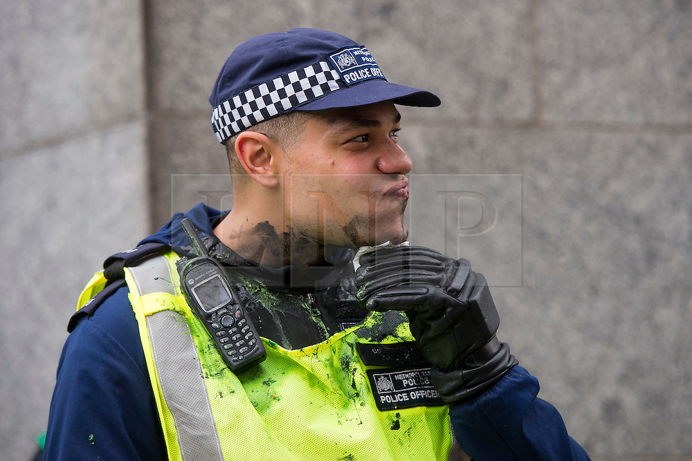 © Licensed to London News Pictures. 04/11/2015. London, UK.  A police officer hit in the face with paint a s Demonstrators clash with police as Thousands of students take part in a demonstration in central London against tuition fees. The rally which starts outside the University of London Union, will feature a speech from Shadow Chancellor John McDonnell.  Photo credit: Ben Cawthra/LNP