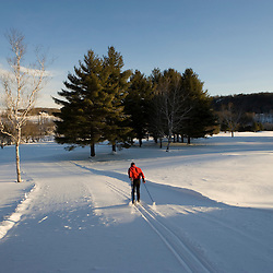 A man cross-country skiing (track skiing) on a groomed trail in Quechee, Vermont.
