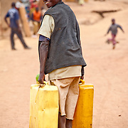 Byukusenge, a young boy in Kisaro, Rulindo District, Rwanda, carries two jerry cans of water back to his home.