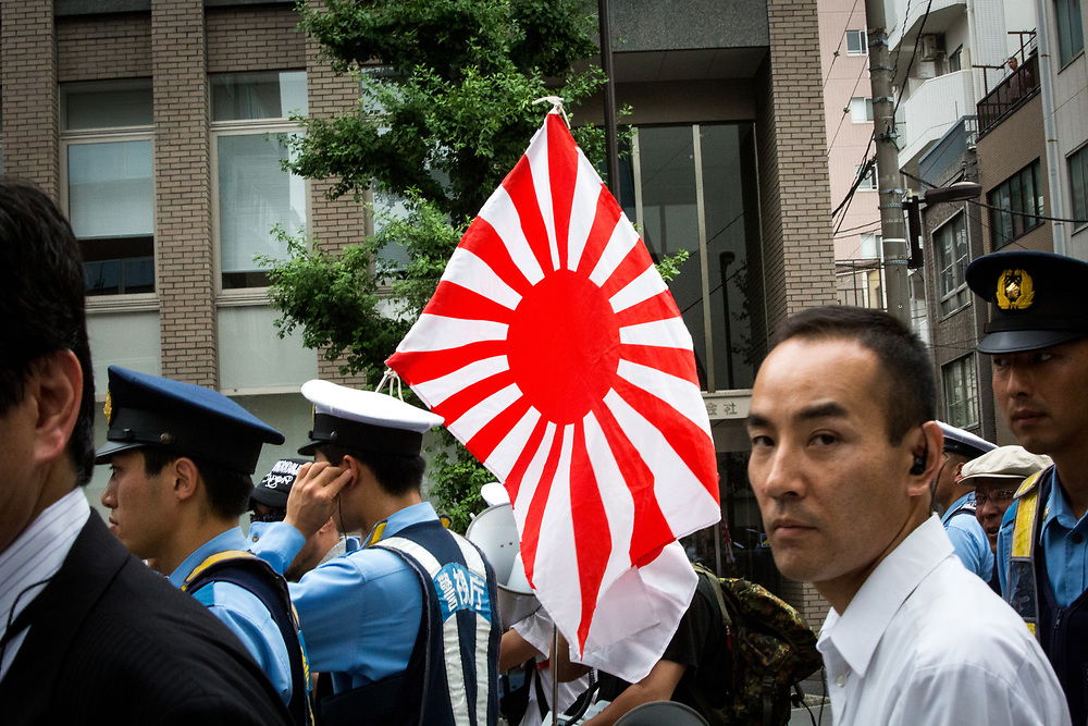 """TOKYO, JAPAN - JULY 16: Japanese nationalists holding Japanese maritime flags, escorted by police, took to the streets in a """"hate demonstration"""" in Akihabara, Tokyo, Japan on July 16, 2017. The nationalists faced off with anti-racist groups who mounted counter protests demanding an end to hate speech and racism in Japan. (Photo by Richard Atrero de Guzman/NUR Photo)"""