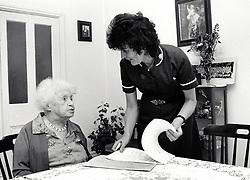 District nurse visiting elderly woman at home, Nottingham UK 1990