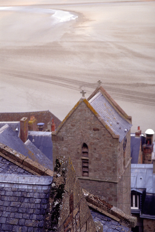 An abstracted view from atop Mont-Saint-Michel overlooking the sandy flats which quickly flood with the racing tidal waters.  The sandy planes contain pockets of quicksand.