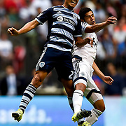 Roger Espinoza (27) collides with Matias Laba during Sporting Kansas City's 1-0 win over the Vancouver Whitecaps at BC Place in Vancouver, B.C., on July 12, 2015.