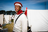 20150614 Ligny Belgium. The Battle of Ligny (16 June 1815) was the last victory of the military career of Napoleon I.Today it was re-enacted by 1500 people just a few days before the 200th birth day of Napoleon's final loss at Waterloo.German re-enactor in white and red stands in the bivouac.