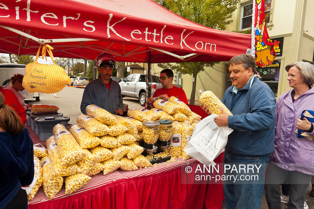 Kettle Corn and lemonade booth at Bellmore Street Fair, with customers buying bags of kettle corn from Keifer's Kettle Corn vendor at colorful red booth, in Bellmore, New York, USA, on September 17, 2011. EDITORIAL USE ONLY