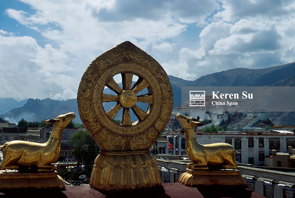 The symbol of reincarnation on the roof of the Jokhang Monastery, Potala Palace and mountain range at back, Lhasa, Tibet, China