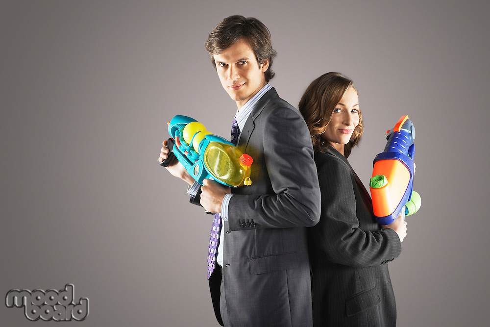 Smiling businesspeople standing back to back holding water guns side view