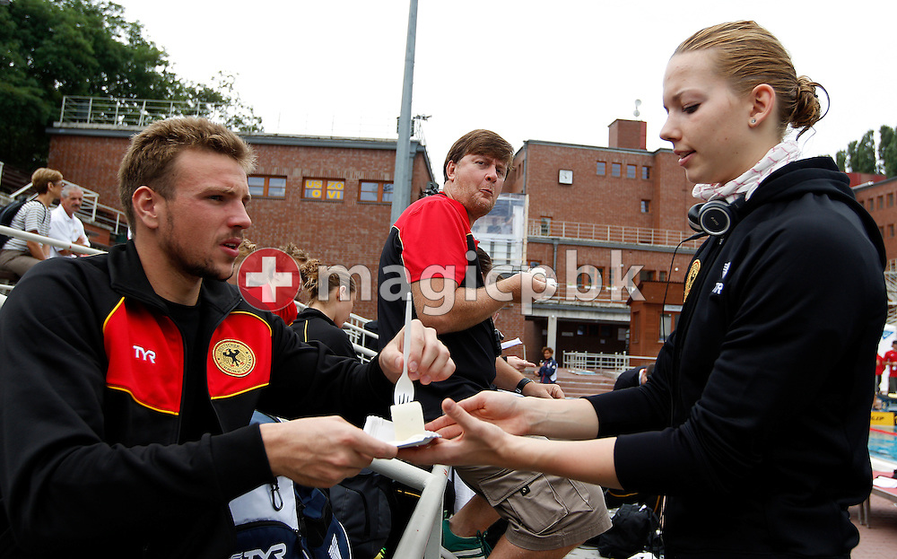Paul BIEDERMANN (L) of Germany gives a pice of his birthday cake that he received from German TV ARD to his 24th birthday to his teammates Daniela SCHREIBER (R), while his coach Frank EMBACHER (C) eats his piece after a training session at the European Swimming Championships in Budapest, Hungary, Saturday, Aug. 7, 2010. (Photo by Patrick B. Kraemer / MAGICPBK)