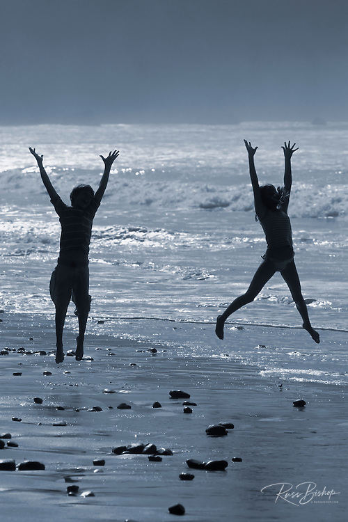 Kids (age 10 & 13) playing in the surf on Sand Dollar Beach (silhouette), Big Sur Coast, California