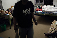 "Bal weariing a ""HIV positive"" T-shirt has just cleaned his room where Ramchandra suffering from tuberculosis is lying in bed. Bal is a former drug user."
