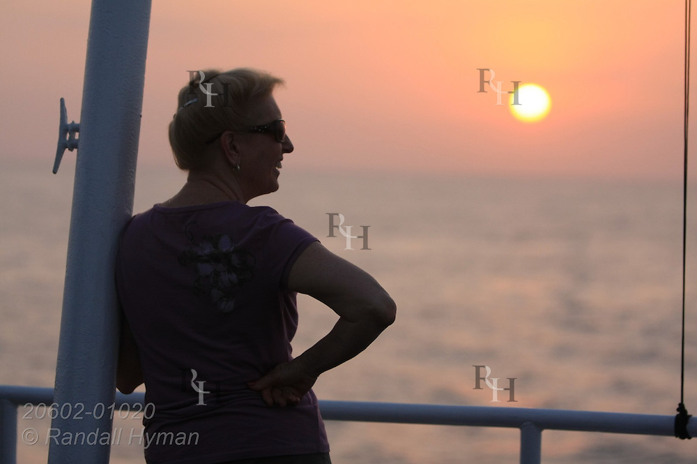 Woman passenger aboard Cruise West's ship Pacific Explorer enjoys a sunset; Costa Rica.