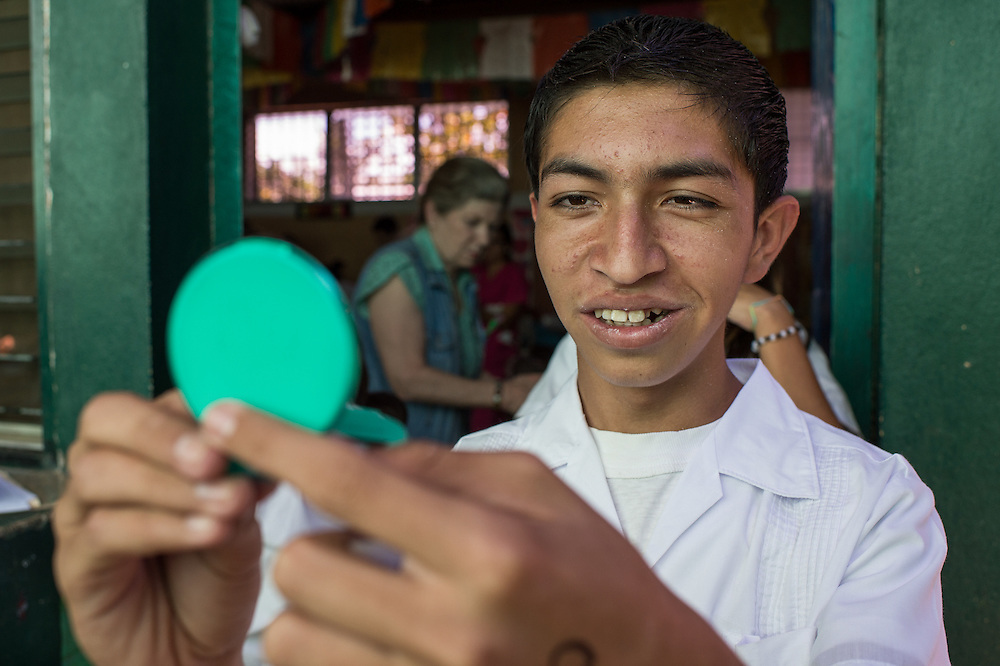 A teenager uses a mirror to look at his front teeth after dentists from Central America Medical Outreach worked at repairing his teeth in La Mariposa Las Flores Lempira, Honduras Feb. 19, 2016. CAMO, Central American Medical Outreach's dental brigade set up a temporary work space in a two room school in La Mariposa Las Flores Lempira, two hours outside of Santa Rosa de Copan. They also provide, gynecological, general medicine, and breast exams during other visits throughout Honduras. Photo Ken Cedeno