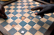 Men playing checkers at a market in Yokadouma, a logging town in the South East Cameroon.