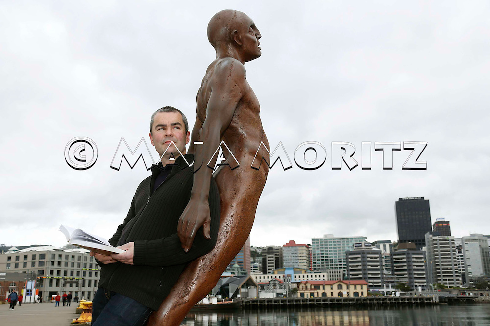 Bernard Beckett at the waterfront in Wellington, New Zealand, leaning at the sculpture Solace in the Wind (Max Patte) which symbolises surrender to the elements