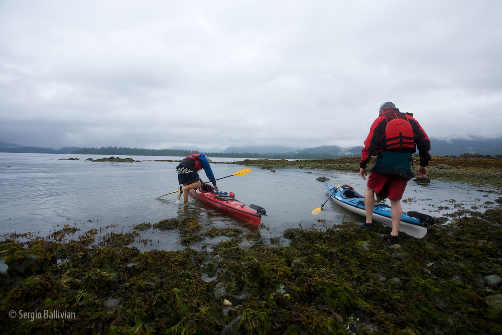 Sea kayakers prepare to launch at low tide under overcast skies in Barkley Sound, BC.
