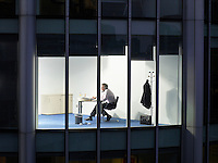 Business man working at desk in office view from building exterior