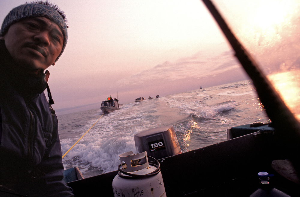Alaska native man captains his boat during a whale hunt