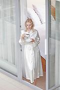 Beautiful young woman in robe having coffee at balcony doorway