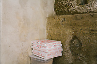 NAPLES, ITALY - 1 AUGUST 2018: Pizza boxes are stacked in the makeshift temporary kitchen of Cantina del Gallo, a family-owned restaurant in the Rione Sanità in Naples, Italy, on August 1st 2018.<br /> <br /> Cantina del Gallo, in the Rione Sanità, was established in 1898 and run by four generations of the Silvestri family. The cantina began as a store selling bulk wine and oil. It was only in the 1950s, when the legendary Aunt Cuncetta began cooking, that it became the simple and genuine tavern it is today.<br /> There are three dishes that are the restaurant's workhorses, and the ones we always seem to rotate between: the pennette alla sorrentina (a variation of the classic gnocchi alla sorrentina, seasoned with tomato, basil and stringy mozzarella), the baked cod (although the fried cod is just as mouth-watering) and the pizza cafona (peasant pizza), topped with oregano, cheese, chile and with double the tomatoes (tomato juice and chopped tomatoes).