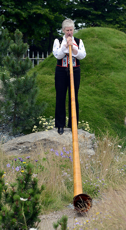 © Licensed to London News Pictures. 02/07/2012. East Molesey, UK A woman blows a swiss horn in the Swiss Alpine Garden. The RHS Hampton Court Palace Flower Show 2012. The show runs 3-8 July, 2012. Photo credit : Stephen Simpson/LNP