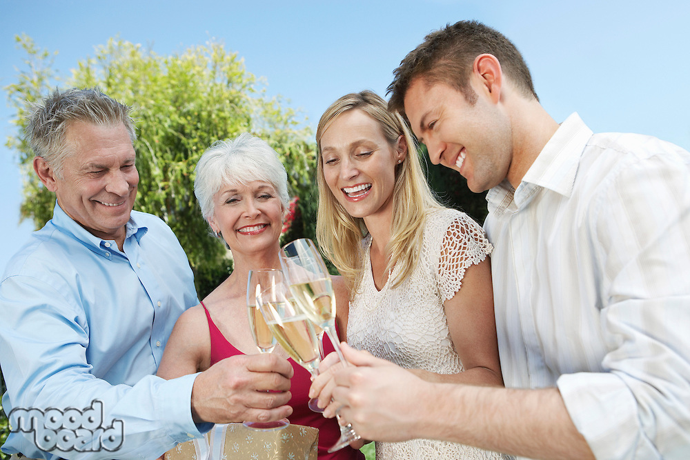 Young couple and older couple Toasting with Champagne outside