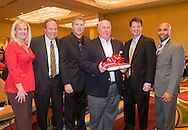 Marie Rudolph, left, Joe Reeder, Steve Beck, University of Maryland head coach Ralph Friedgen, center, Kirby Smith, and Erik Moses, right, pose for a photo during the welcome reception for the University of Maryland football team at the Renaissance Hotel in Washington, DC, where they will be staying for the Military Bowl. They will face East Carolina University in the Military Bowl on December 29, 2010. (Photo by Alan Lessig)