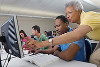 Teacher helping student in computer class