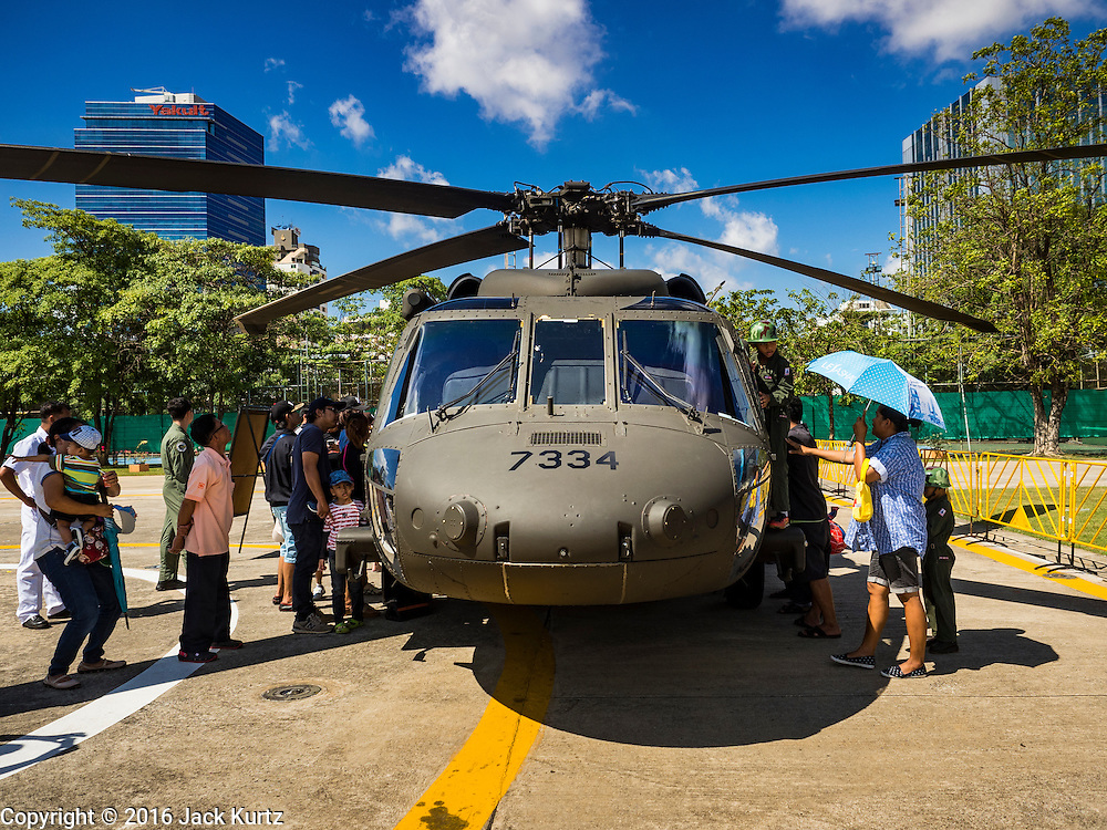 09 JANUARY 2016 - BANGKOK, THAILAND: People look at a Thai Army Blackhawk helicopter during Children's Day festivities at the Royal  Thai Army's Palace Guard, 2nd Division Cavalry Base in Bangkok. National Children's Day falls on the second Saturday of the year. Thai government agencies sponsor child friendly events and the military usually opens army bases to children, who come to play on tanks and artillery pieces.         PHOTO BY JACK KURTZ