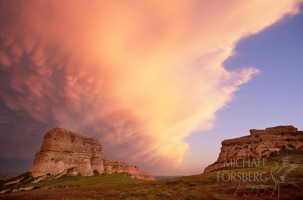 Courthouse and Jail Rocks, Nebraska Panhandle.  At twilight, bubble-shaped lenticular clouds boil in the sky signaling a brewing storm cell heading east over Courthouse and Jail Rocks, one of many sandstone monoliths that rise out of the prairie along the North Platte River valley in western Nebraska. Summer home to golden eagles and prairie falcons, such formations were revered by Plains Indians cultures and were the first vertical relief seen for weeks by early pioneers as they traveled the Oregon Trail west in the 1800's.