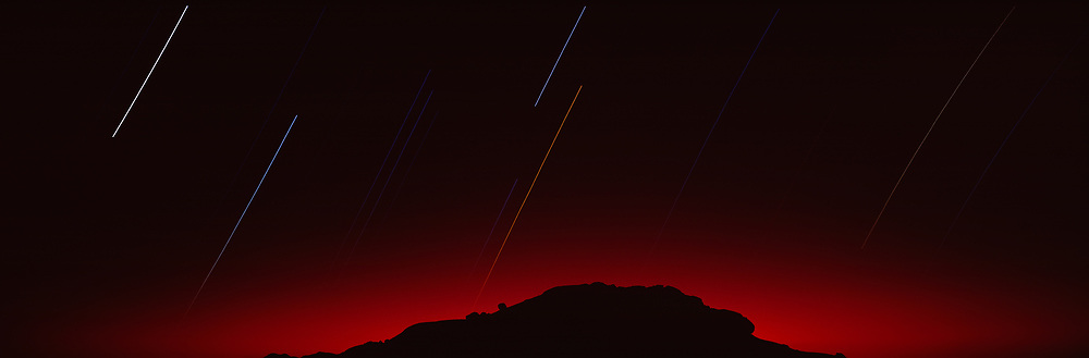 Mountain at night with star trails and red sky