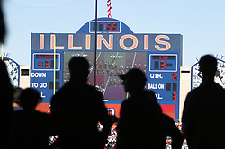 Scoreboard at Memorial stadium at the University of Illinois in Champaign - Urbana.  Shot is looking out at field from near photographers area under the horseshoe.  Many people are sillouetted in foreground.
