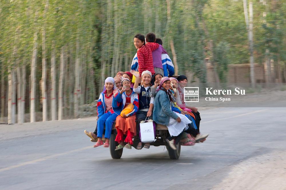 Uighur children go to school on motorbike taxi, Hotan, Xinjiang, China