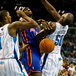 December 3, 2010; New Orleans, LA, USA; New York Knicks power forward Amare Stoudemire (1) loses the ball in a collision with New Orleans Hornets center Emeka Okafor (50) and small forward Trevor Ariza (1) during the second half at the New Orleans Arena. The Knicks defeated the Hornets 100-92. Mandatory Credit: Derick E. Hingle