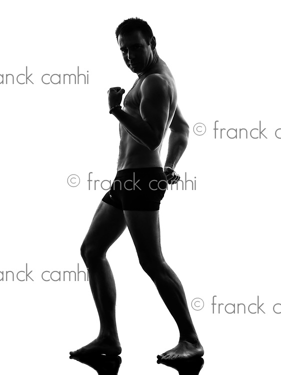 one caucasian mature in underwear man flexing muscles in silhouette on white background