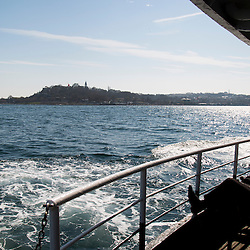 A view from the ferry that connects Karakoy on the European side of Istanbul to Kadikoy on the Asian side of the city. In the distance is the old city, where the Blue Mosque and Aya Sofia are located. The ferry crosses the Bosphorus Strait.