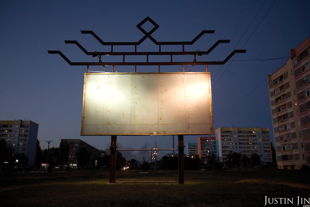 An empty billboard stands in Elista, capital of the southern Russian republic Kalmykia...The republic is run by Kirsan Ilyumzhinov, 44, a millionaire businessman and president of the World Chess Federation, Fide...Ilyumzhinov is hosting one of the world's most important matches in history. The, match beginning September 21 in Elista, will end a 13-year split in the game that has produced rival claims to the title. ..Veselin Topalov, a Bulgarian ranked first according to Fide, will play against Vladimir Kramnik, who is the Classical Chess World Champion, a title established after Garry Kasparov led a breakaway from Fide in 1993. The two grandmasters, both aged 31, will face each other for the right to be undisputed world chess champion...Ilyumzhinov acquired his wealth in the economic free-for-all which followed the collapse of the Soviet Union. ..At the age of just over 30, he was elected president in 1993 after promising voters $100 each and a mobile phone for every shepherd. Soon after, he introduced presidential rule, concentrating power in his own hands. ..He denies persistent accusations of corruption, human rights abuses and the suppression of media freedom. When Larisa Yudina, editor of the republic's only opposition newspaper and one of his harshest critics, was murdered in 1998, he strenuously rejected allegations of involvement. ..Mr Ilyumzhinov has been president of the International Chess Federation (FIDE) since 1995 and has been enthusiastic about attracting international tournaments to Kalmykia. His extravagant Chess City has led to protests by its impoverished citizens. ...
