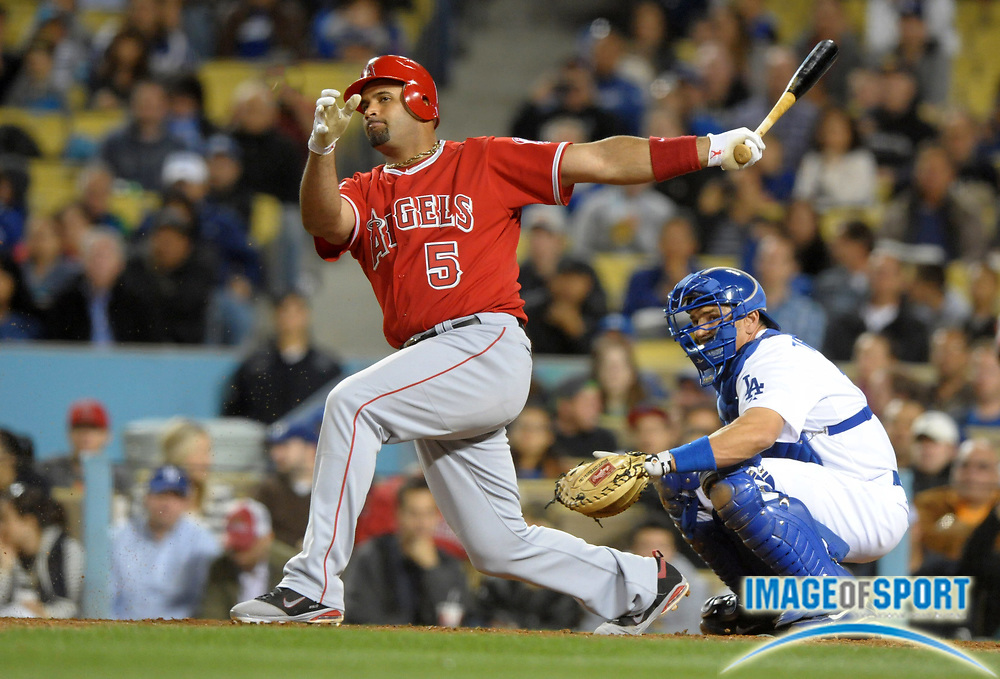 Apr 3, 2012; Los Angeles, CA, USA; Los Angeles Angels first baseman Albert Pujols (5) follows through on a run-scoring sacrifice fly ball in the sixth inning against the Los Angeles Dodgers at Dodger Stadium.