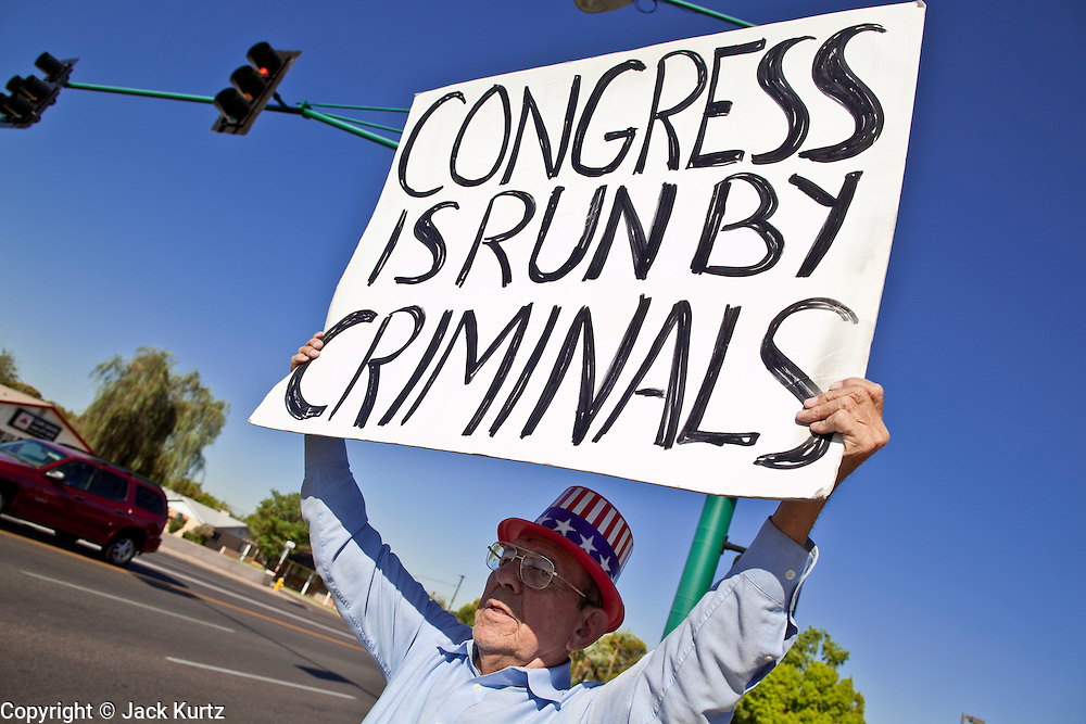 "July 6 - PHOENIX, AZ:  Frank Trejo, from Phoenix, pickets a street corner in Phoenix Tuesday morning to protest the federal budget deficit and Congressional inaction on immigration reform. Trejo pickets a different corner in central Phoenix every morning. He said he is not a member of the Tea Party, but that he is ""digusted"" with both political parties and agrees with many of the Tea Party ideals.    Photo by Jack Kurtz"