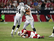 Oakland Raiders rookie defensive end Drew Iddings (69) celebrates with Oakland Raiders defensive end Greg Townsend (94) after Iddings sacks Arizona Cardinals quarterback Jake Coker (6) on a fourth down play late in the fourth quarter during the 2016 NFL preseason football game against the Arizona Cardinals on Friday, Aug. 12, 2016 in Glendale, Ariz. The Raiders won the game 31-10. (©Paul Anthony Spinelli)