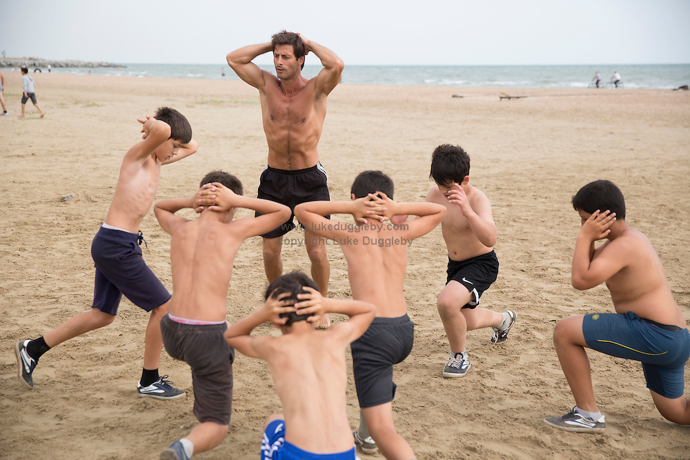 Young buys are taught wrestling on a beach by the Caspian Sea. Fighting is embedded in to the culture of Dagestan and it is renowned around the world for producing large numbers of great fighters from wrestlers to mixed martial arts. The Russian government in Moscow also sends large amounts of funding to help train such fighters. <br /> <br /> Located in the North Caucasus, bordering the Caspian Sea and a Republic of Russia, Dagestan is home to almost 3 million mostly muslim people. Ethnically very diverse, it is made up of several dozen ethnic groups and is Russia's most heterogeneous republic, where no ethnicity forms a majority.<br /> <br /> From 2000 until late 2012 Dagestan was subject to a violent Islamic separatist movement that spilled over from neighbouring Chechnya but has now been largely controlled by the Russian Government.<br /> <br /> Now relatively peaceful Dagestan (which means Land of Mountains) remains one of Russia's untouched treasures receiving few visitors. Due to its relative isolation, this beautiful mountainous region has maintained its traditional cultures that have been lost in many other parts of Russia.