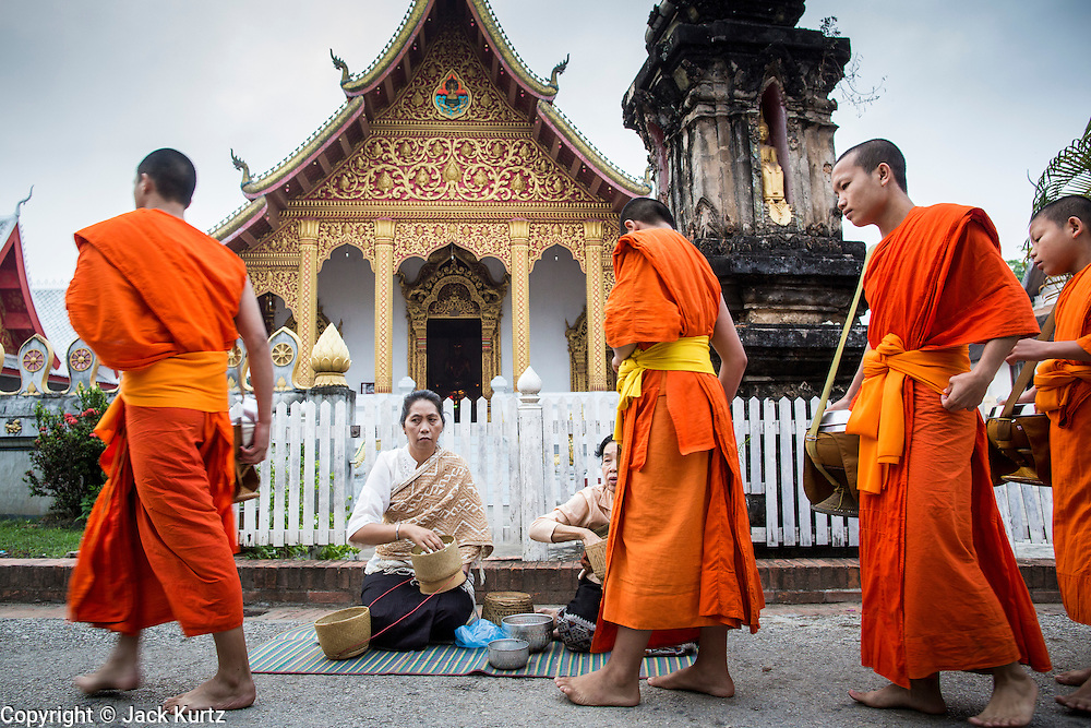 """11 MARCH 2013 - LUANG PRABANG, LAOS: Buddhist monks walk past Wat Nong Sikhounmuang and collect alms during the tak bat in Luang Prabang. The """"Tak Bat"""" is a daily ritual in most of Laos (and other Theravada Buddhist countries like Thailand and Cambodia). Monks leave their temples at dawn and walk silently through the streets and people put rice and other foodstuffs into their alms bowls. Luang Prabang, in northern Laos, is particularly well known for the morning """"tak bat"""" because of the large number temples and monks in the city. Most mornings hundreds of monks go out to collect alms from people.    PHOTO BY JACK KURTZ"""