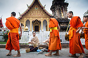 "11 MARCH 2013 - LUANG PRABANG, LAOS: Buddhist monks walk past Wat Nong Sikhounmuang and collect alms during the tak bat in Luang Prabang. The ""Tak Bat"" is a daily ritual in most of Laos (and other Theravada Buddhist countries like Thailand and Cambodia). Monks leave their temples at dawn and walk silently through the streets and people put rice and other foodstuffs into their alms bowls. Luang Prabang, in northern Laos, is particularly well known for the morning ""tak bat"" because of the large number temples and monks in the city. Most mornings hundreds of monks go out to collect alms from people.    PHOTO BY JACK KURTZ"